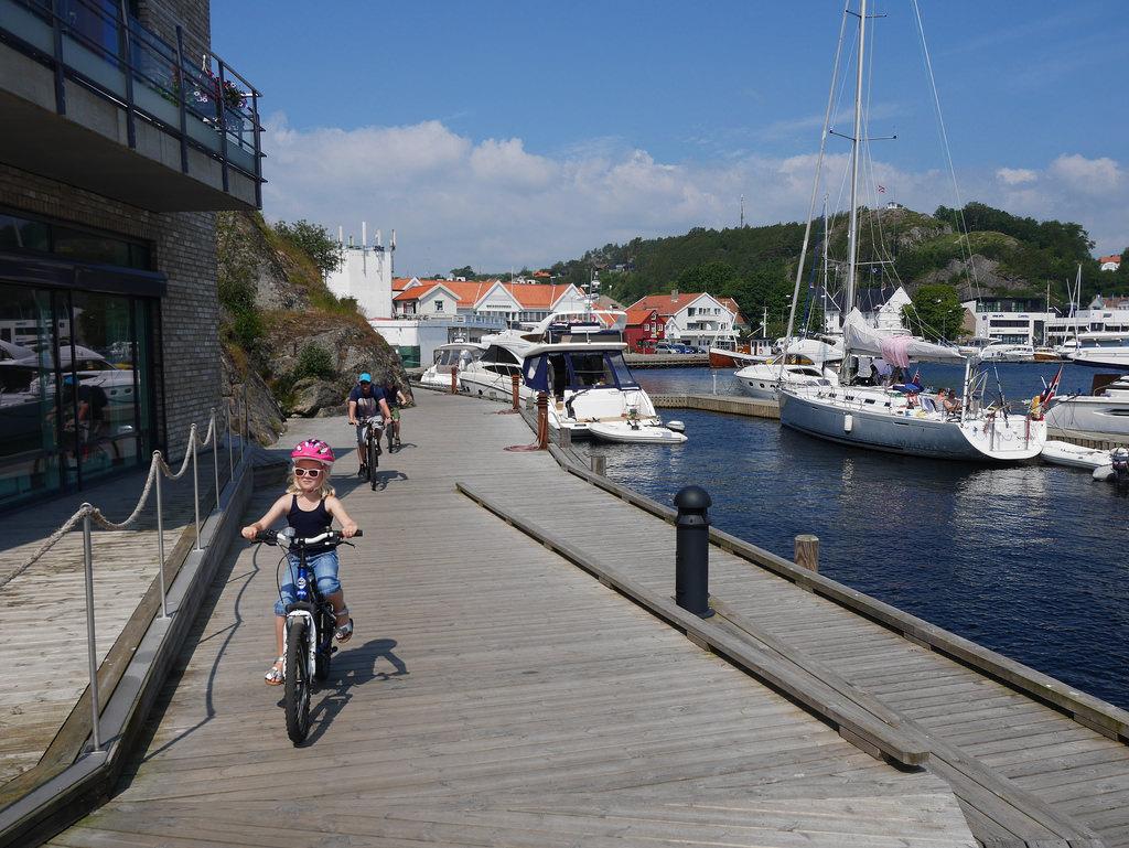 Start sykkelturen med å sykle langs elvepromenaden i Mandal sentrum.