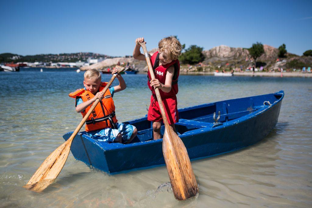 På sommerleir på Barnas Øy. Gutter som padler i liten båt på Bragdøya utenfor Kristiansand