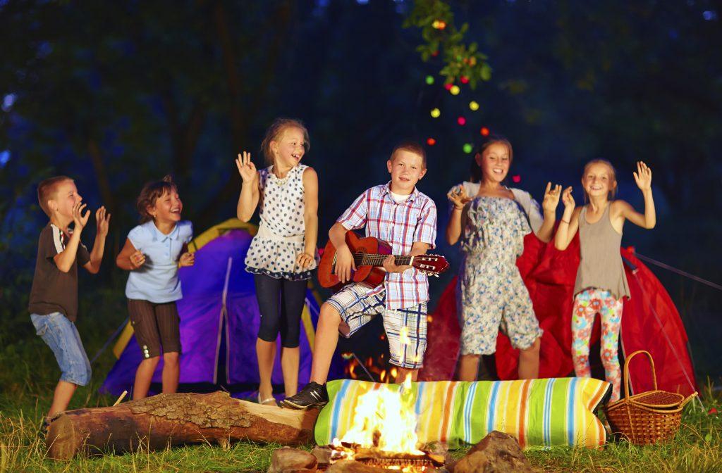 Barn som danser rundt leirbålet på sommerleir