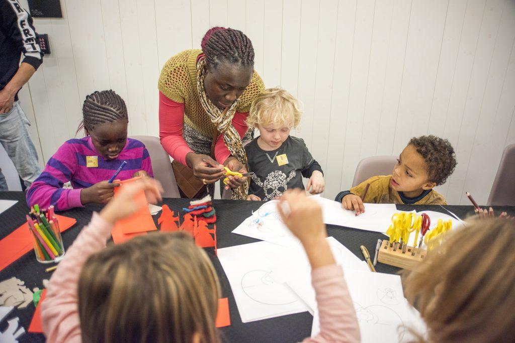 Barn og voksne i full gang med å lage julegaver og julepynt. Foto: Kuben