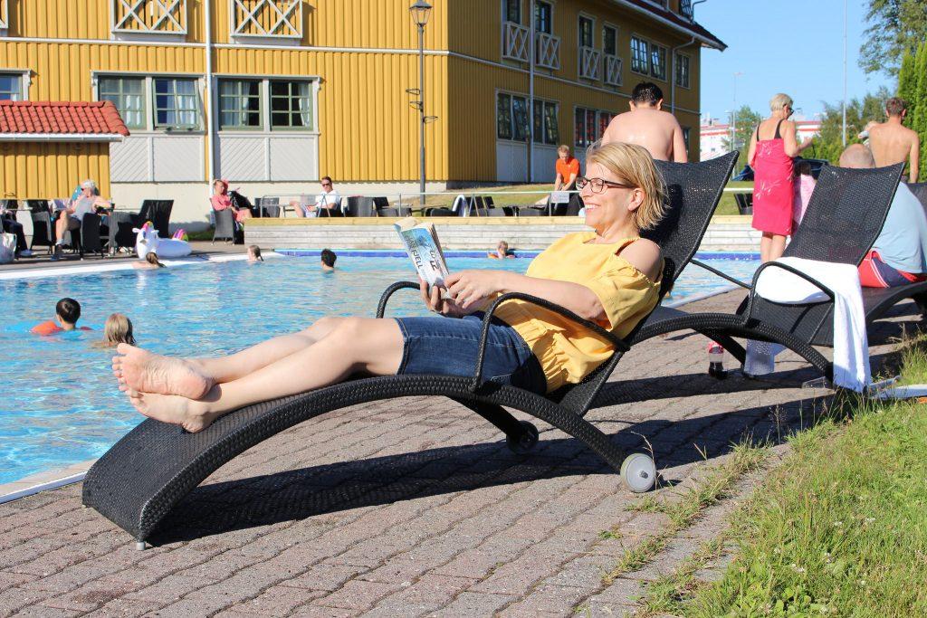 Mamma koser seg med bok ved bassenget på Scandic Sørlandet