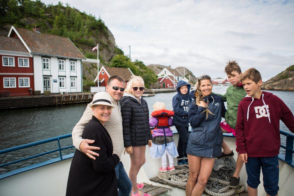voksne og barn ombord på båt gjennom Ny-Hellesund